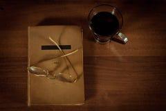 Buch auf dem Tisch, Gläser und eine Schale Lizenzfreie Stockbilder