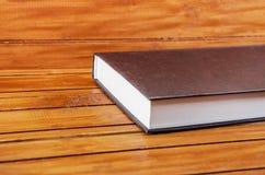 Buch auf einem braunen Holztisch lizenzfreies stockbild