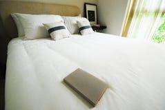 Buch auf weißem Bett Stockfotografie