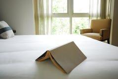 Buch auf weißem Bett Lizenzfreie Stockfotos