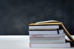 Buch auf weißem Tabellenschwarz-Bretthintergrund Stockfotos