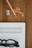 Buch, Bleistift, Schauspiele, Skala, Bleistift und Bleistiftspitzer auf Holztisch Stockbilder