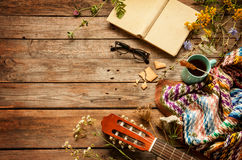 Buch, Decke, Kaffee und klassische Gitarre auf Holz Lizenzfreie Stockfotografie