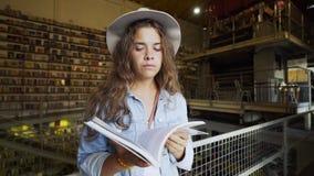 Buch der jungen Frau Lesein der Bibliothek stock video