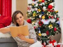 Buch der jungen Frau Lesenahe Weihnachtsbaum Lizenzfreies Stockfoto