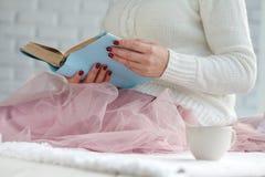 Buch der jungen Frau Leseund Aalen mit Plaid und Kaffee Stockbilder