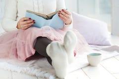 Buch der jungen Frau Leseund Aalen mit Plaid und Kaffee Stockfotografie