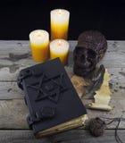 Buch der schwarzen Magie mit mystischen Gegenständen lizenzfreie stockfotos