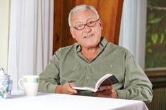 Buch des älteren Mannes Leseim Rest Lizenzfreies Stockbild
