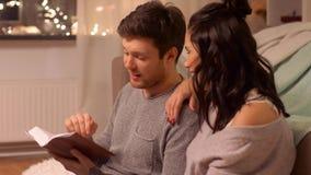 Buch des glücklichen Paars Lesezu hause stock footage