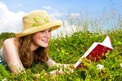 Buch des jungen Mädchens Lesein der Wiese Stockfotografie