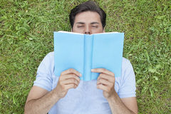 Buch des jungen Mannes Lesebeim Lügen auf Gras Lizenzfreie Stockfotografie