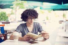 Buch des jungen Mannes Leseim Café Stockbild