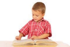 Buch des kleinen Jungen Leseauf dem Schreibtisch Stockfotos