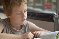 Buch des kleinen Jungen Leseim freien, in der Stadt Lizenzfreie Stockfotografie