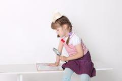 Buch des kleinen Mädchens Lesebeim Sitzen an der Bank Stockfoto