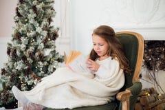 Buch des kleinen Mädchens Lesenahe Weihnachtsbaum stockbilder