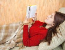 Buch des recht jungen Mädchens Leseauf Sofa stockbild