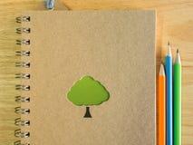 Buch gemacht durch Recyclingpapier und bunte Bleistifte auf hölzernem Schreibtisch Lizenzfreie Stockbilder