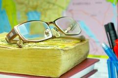 Buch, Gläser und Karte Stockfotografie