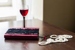 Buch, Glas Wein, Perlen Stockfotografie