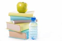 Buch, grüner Apfel und Wasser Stockfotos