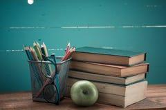 Buch mit Apfel- und Bleistiftkasten Lizenzfreie Stockfotos