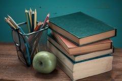 Buch mit Apfel- und Bleistiftkasten Lizenzfreie Stockfotografie