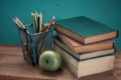 Buch mit Apfel- und Bleistiftkasten Lizenzfreies Stockfoto