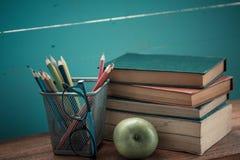 Buch mit Apfel- und Bleistiftkasten Lizenzfreie Stockbilder