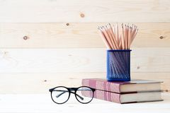 Buch mit Bleistiften im Korb und im eyeglassesl Stockbild