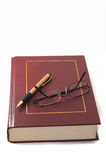 Buch mit Feder und Gläsern Stockfotografie