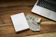 Buch mit Geld und Laptop Lizenzfreies Stockfoto