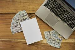 Buch mit Geld und Laptop Stockbilder