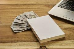 Buch mit Geld und Laptop Stockbild