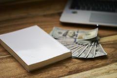 Buch mit Geld und Laptop Stockfoto