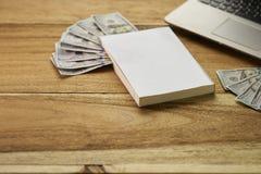 Buch mit Geld und Laptop Lizenzfreie Stockfotografie