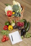 Buch mit Gemüse und Korb Lizenzfreie Stockbilder