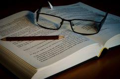 Buch mit Gläsern und Bleistift Stockfotografie