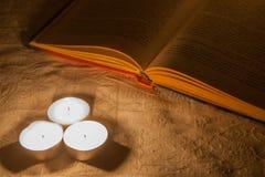 Buch mit Kerze Stockfotos