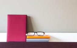 Buch, Notizbücher und Gläser auf Regal Stockfotografie