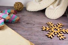 Buch, Schneeflocke, strickte Socken und mittenson hölzernen Hintergrund Stockbilder