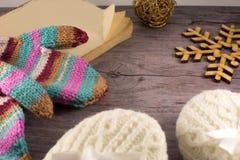 Buch, Schneeflocke, strickte Socken und mittenson hölzernen Hintergrund Stockfotos