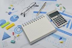 Buch, Stift, Taschenrechner, Gläser auf Finanzdiagramm Lizenzfreies Stockfoto