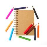 Buch und bunte Bleistifte lokalisiert auf weißem Hintergrund Lizenzfreie Stockfotos