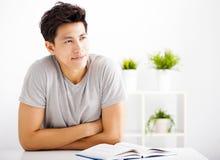 Buch und -c$denken des jungen Mannes Lese Lizenzfreies Stockfoto