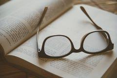 Buch und Gläser Abbildung der roten Lilie Stockfotografie