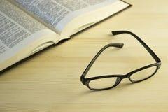 Buch und Gläser auf einem Holztisch Stockbild