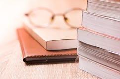 Buch und Gläser auf hölzerner Tabelle Stockfotos