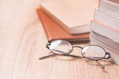 Buch und Gläser auf hölzerner Tabelle Lizenzfreies Stockbild